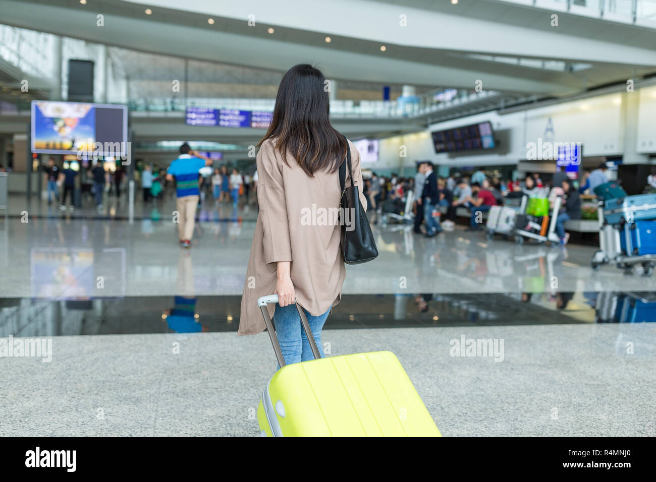 Back view of woman with her luggage in airport - Stock Image