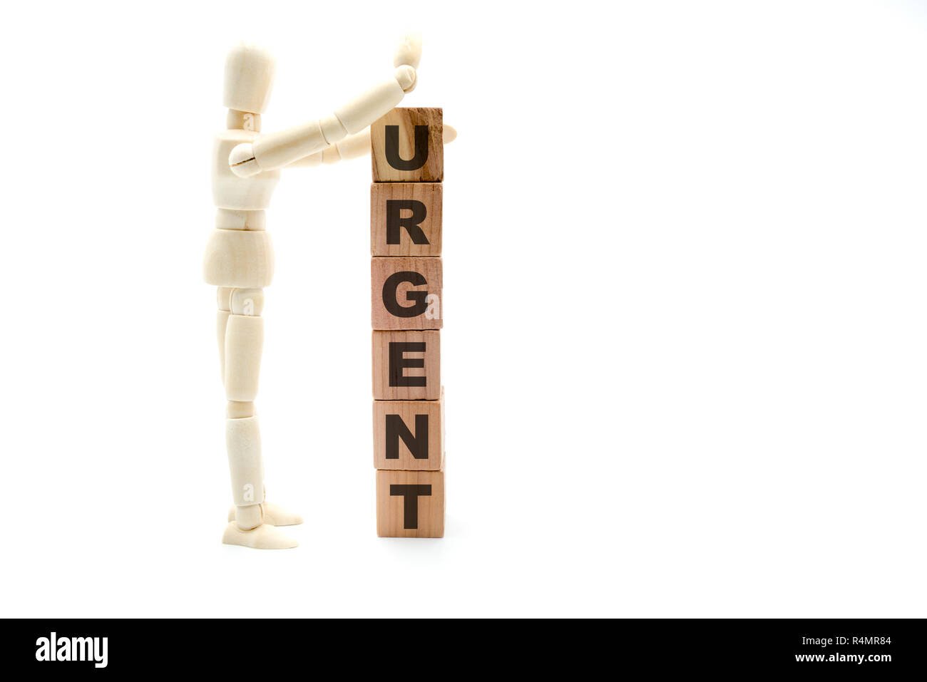 Wooden figure as businessman building Urgent concept as tower of wood cubes, isolated on white background Stock Photo