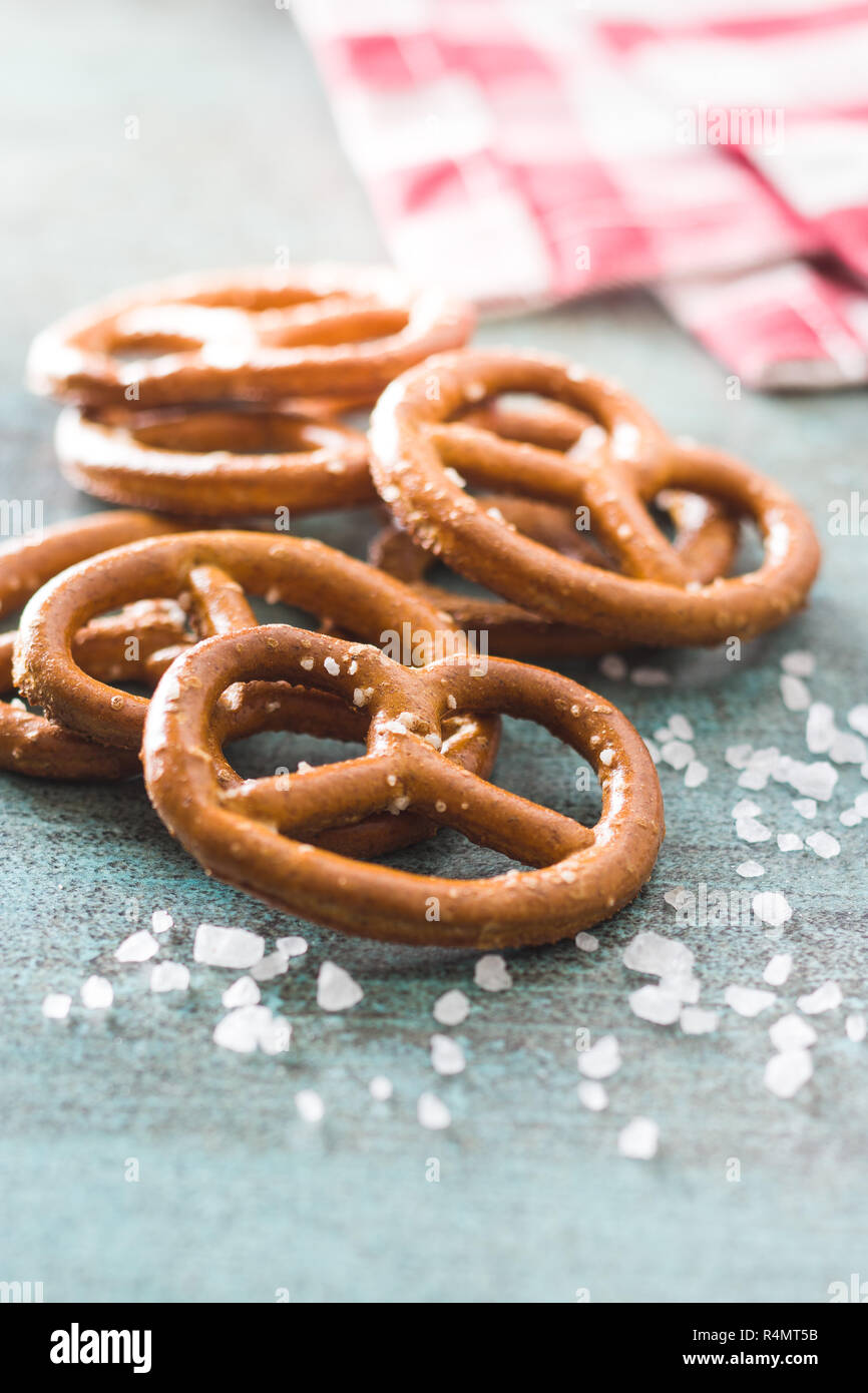 Salted mini pretzels snack on old kitchen table. - Stock Image