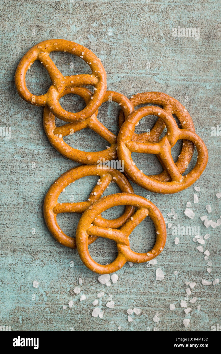Salted mini pretzels snack on old kitchen table. Top view. - Stock Image
