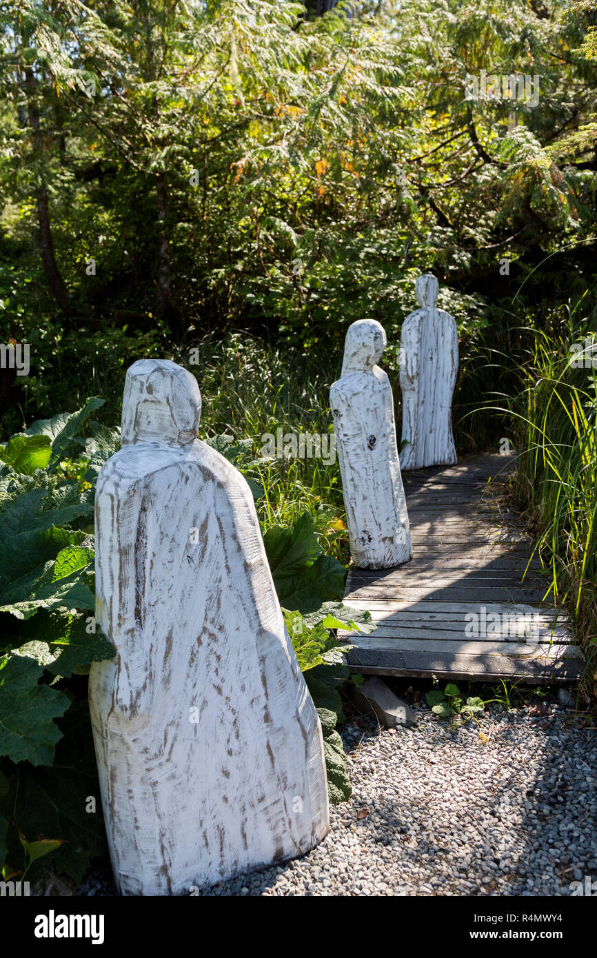 Carved human figures on the edge of woodland, Tofino gardens, Tofino, Vancouver Island, Pacific Rim National Park Reserve, British Columbia, Canad - Stock Image