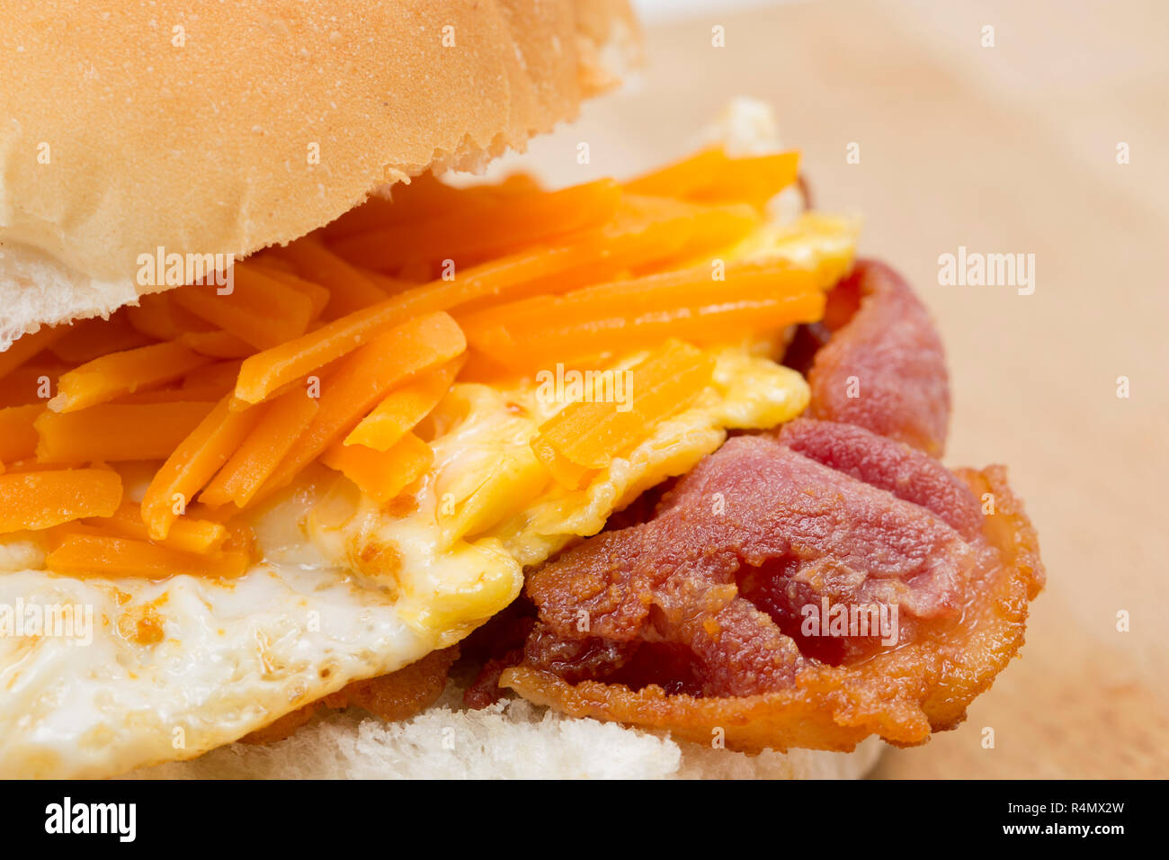 Smoked back bacon produced in the EU and bought from a UK supermarket that has been fried and placed on a bread roll with a fried egg and a sprinkling - Stock Image