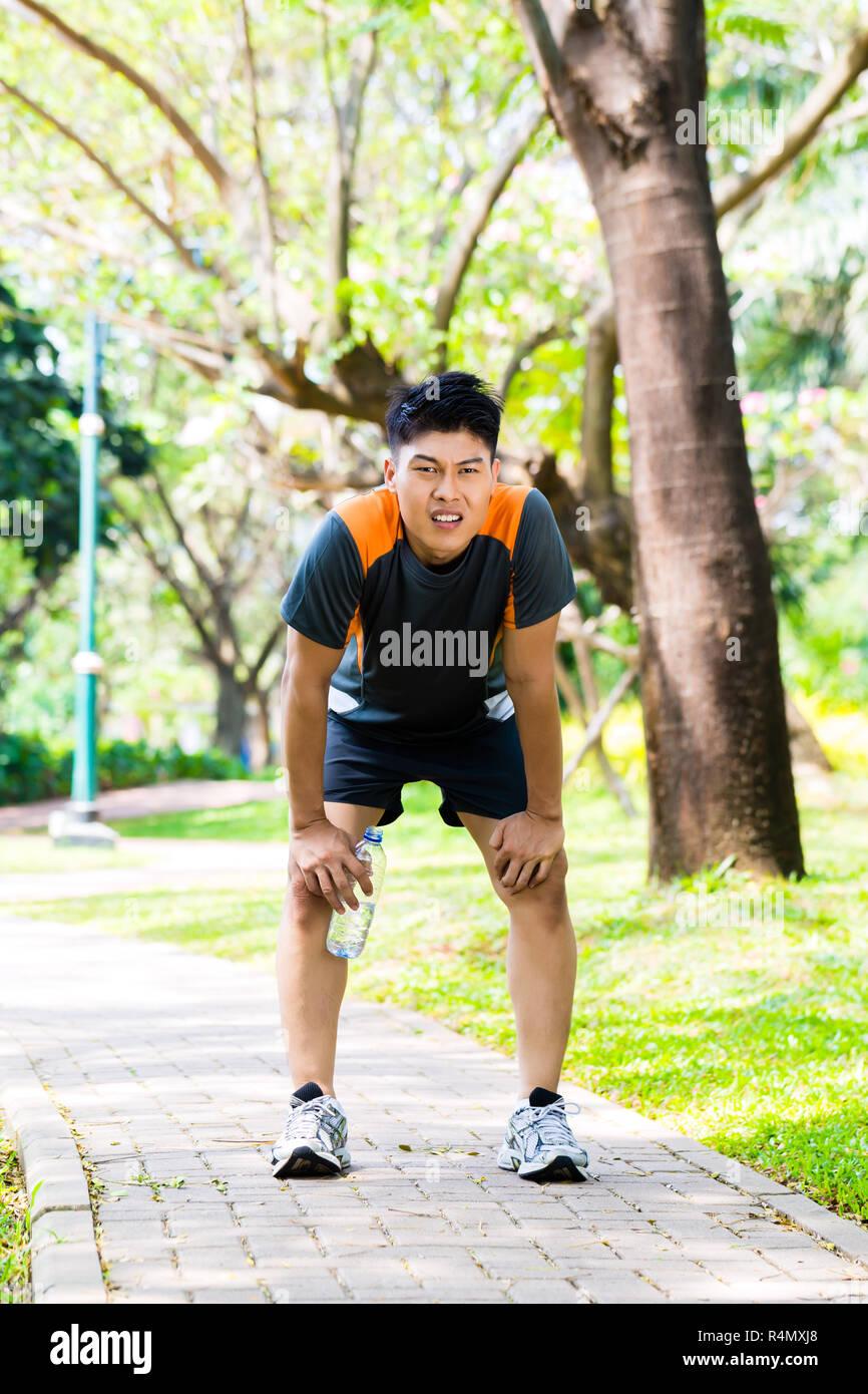 Asian man take breathless break of running - Stock Image