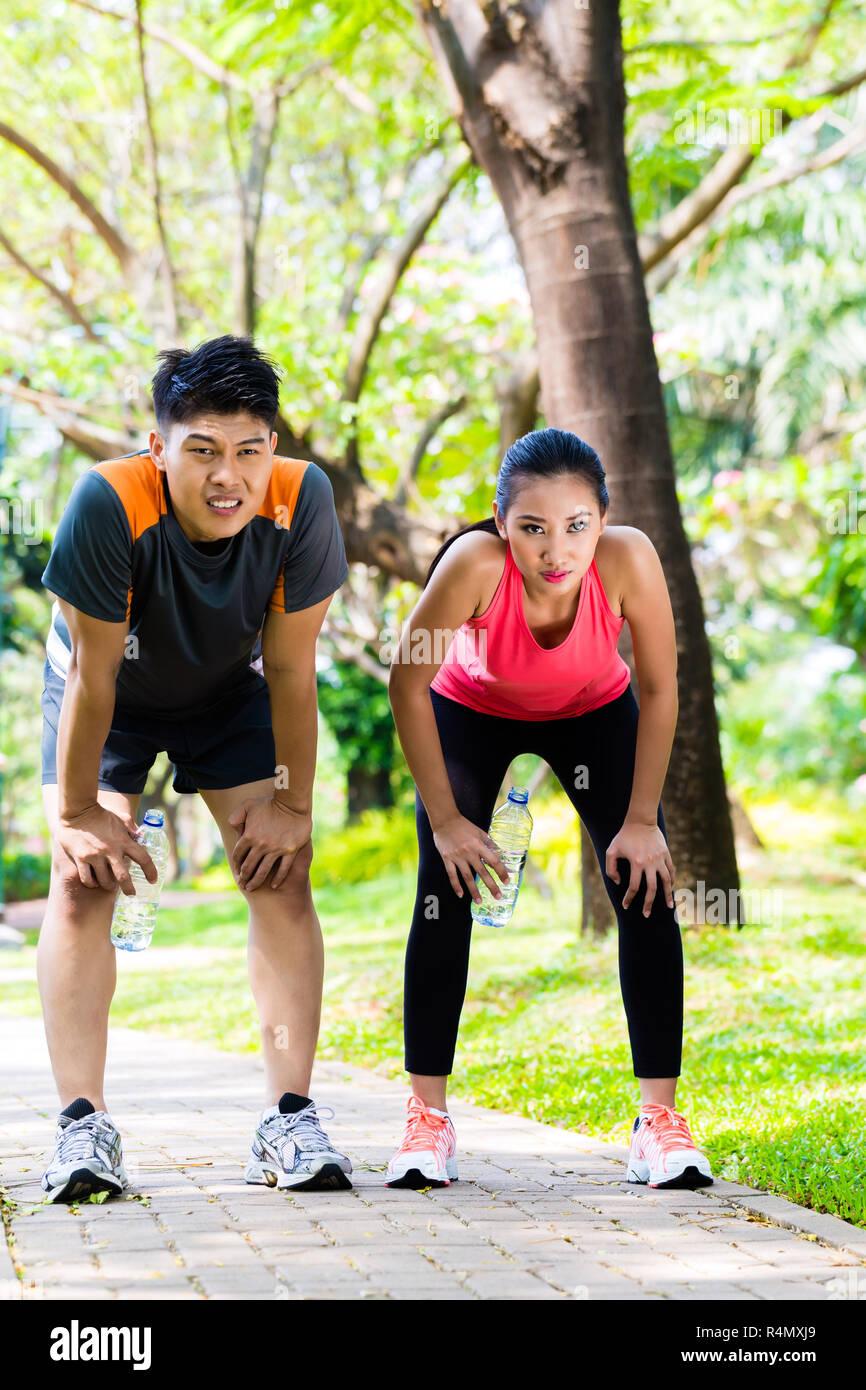 Asian couple take breathless break from running - Stock Image