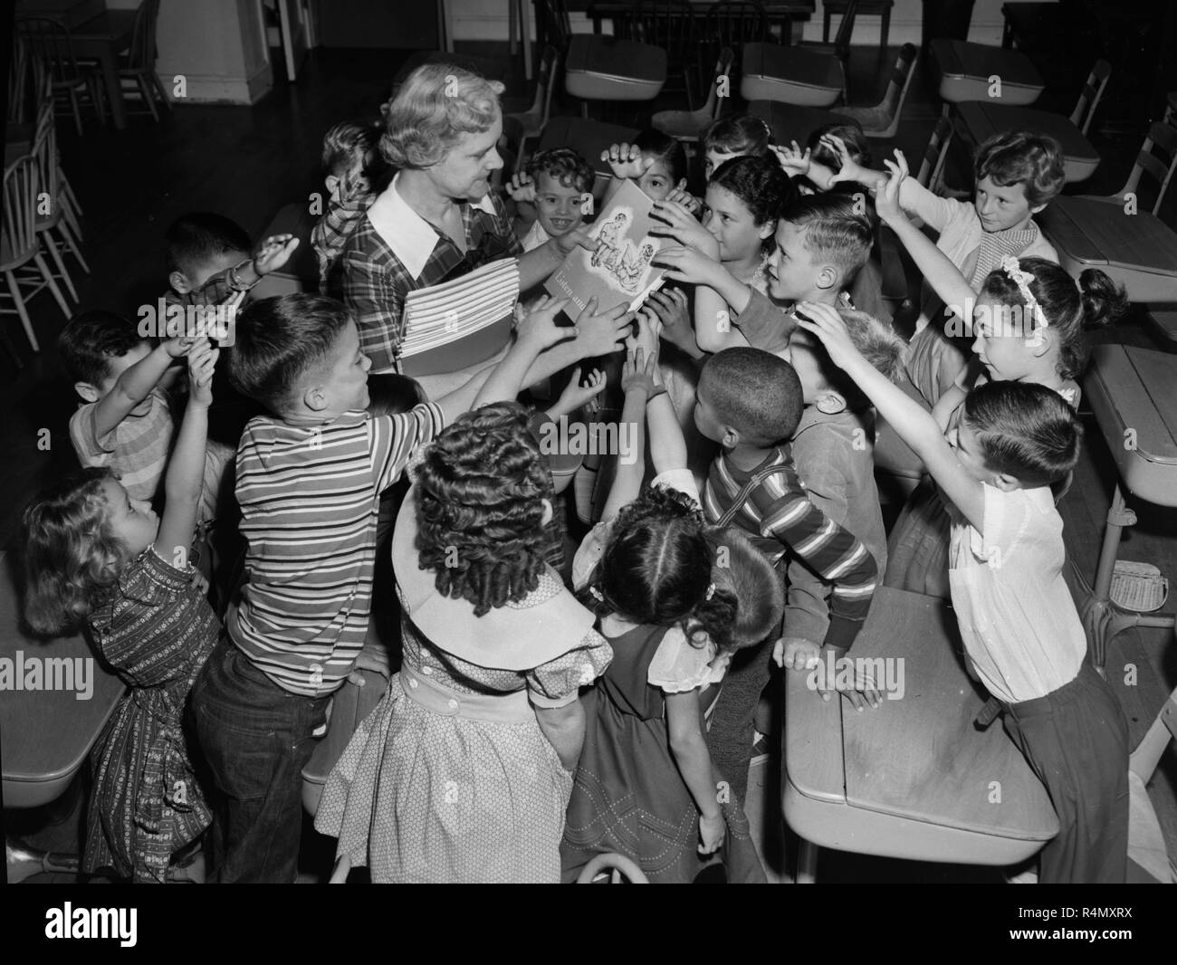 School children reach out for a book from a teacher on the first day of school, ca. 1956. - Stock Image