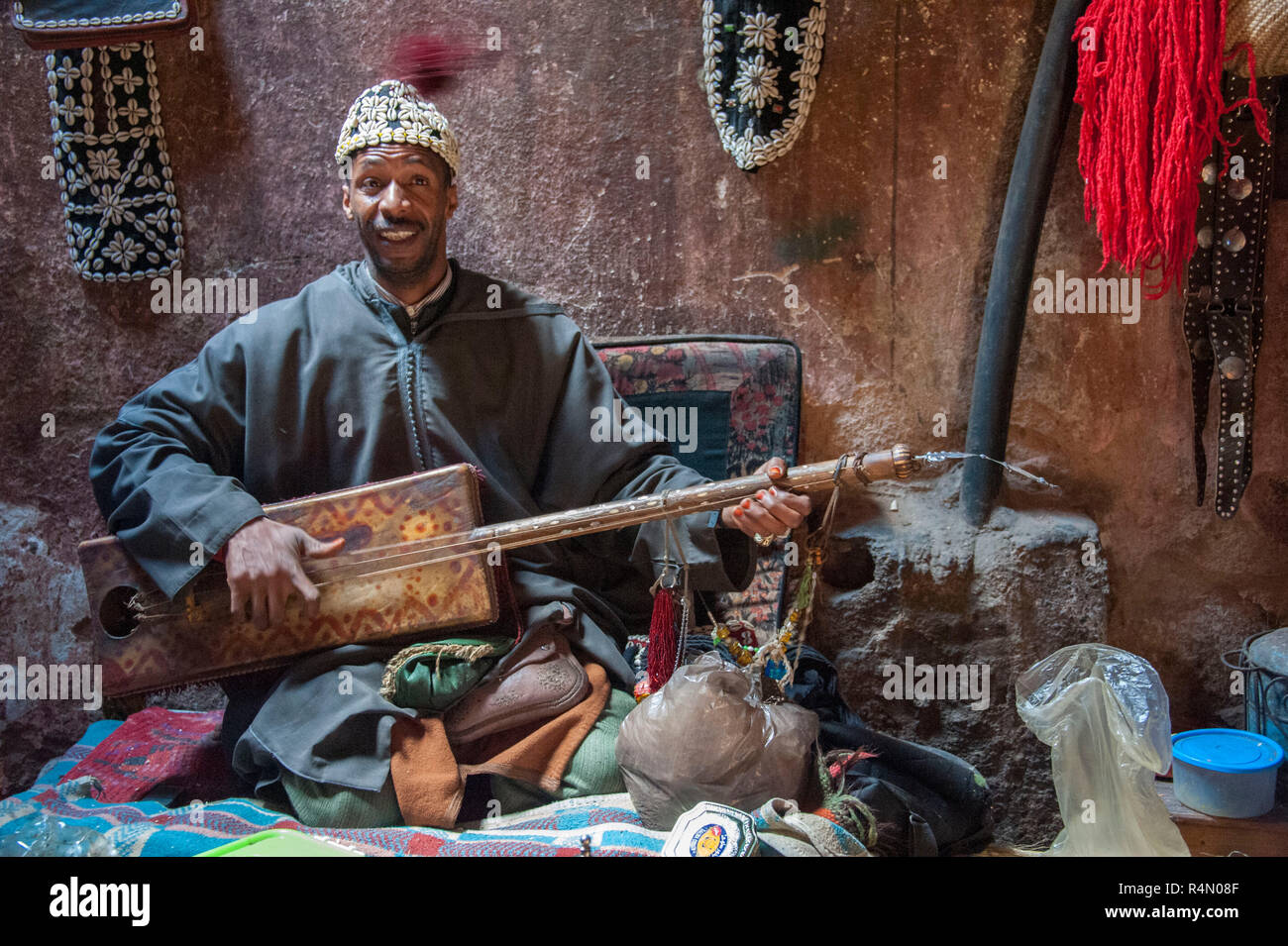 18-04-11. Marrakech, Morocco. A musician sitting cross legged and playing a traditional three stringed guembri musical instrument. He wears a fez hat - Stock Image