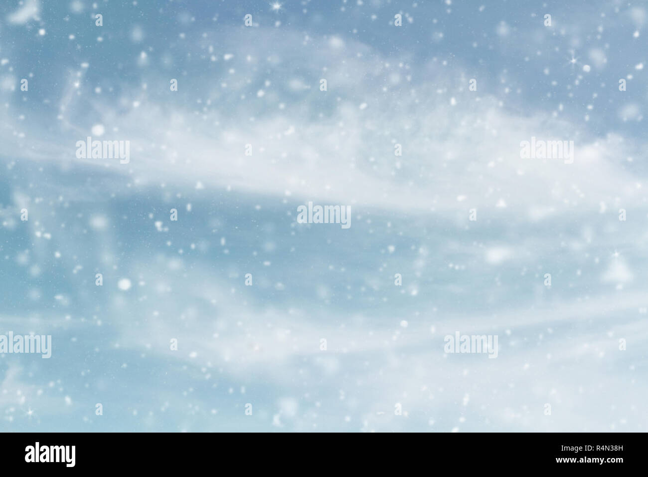 Snowy wintry sky. Blurred background of snow falling against cool blue cloudy sky during a winter storm. - Stock Image