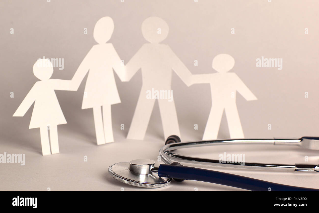 stethoscope and the family paper doll.the concept of health. - Stock Image