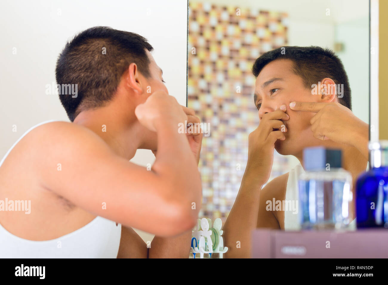 Asian man discovering a pimple in face - Stock Image