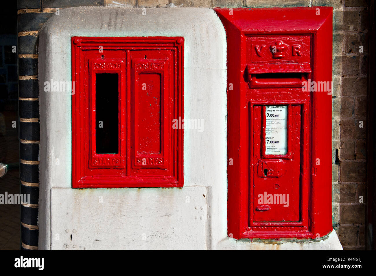 A wall mounted  Victorian post box alongside an unused Type E stamp vending machine at Lowestoft Railway Station in Suffolk, UK - Stock Image