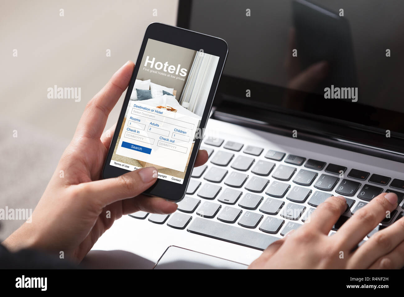 Person Booking Hotels Using Cell Phone - Stock Image