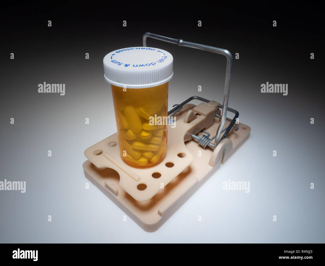 Mousetrap with medical bottle full of pills. Drug cost and addiction concept. - Stock Image
