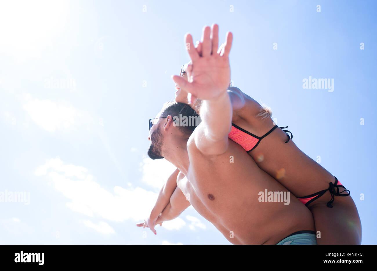 Man carrying woman piggyback on beach. - Stock Image