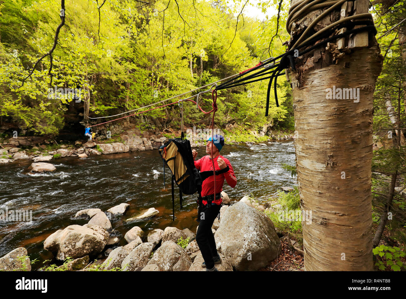 Climber traversing across the Au Sable River to access the climbing a route on Moss Cliff above Wilmington Notch, Adirondack Mountains, New York State, USA - Stock Image