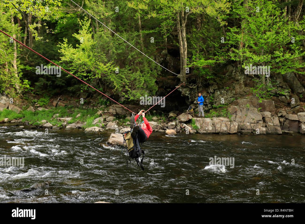 Climber traversing across the Au Sable River to access the climbing a route on Moss Cliff above Wilmington Notch, Adirondack Mountains, New York State, USA Stock Photo