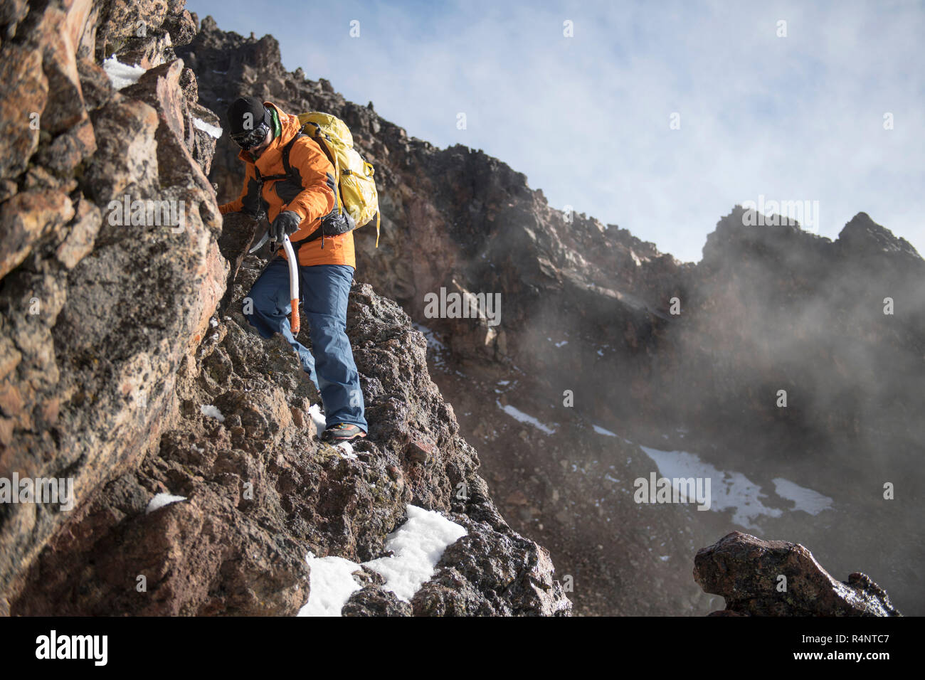 One man climbs trough a rocky section using a piolet, or ice axe, on his ascent to the Iztaccihuatl volcanoe at the Izta-Popo Zoquiapan National Park in Puebla, Mexico Stock Photo