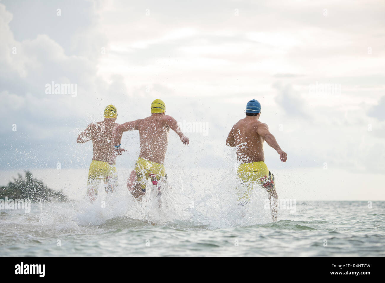 ca93a6e154c Rear view of three men in swimming caps and swimming trunks running into  sea at Playa