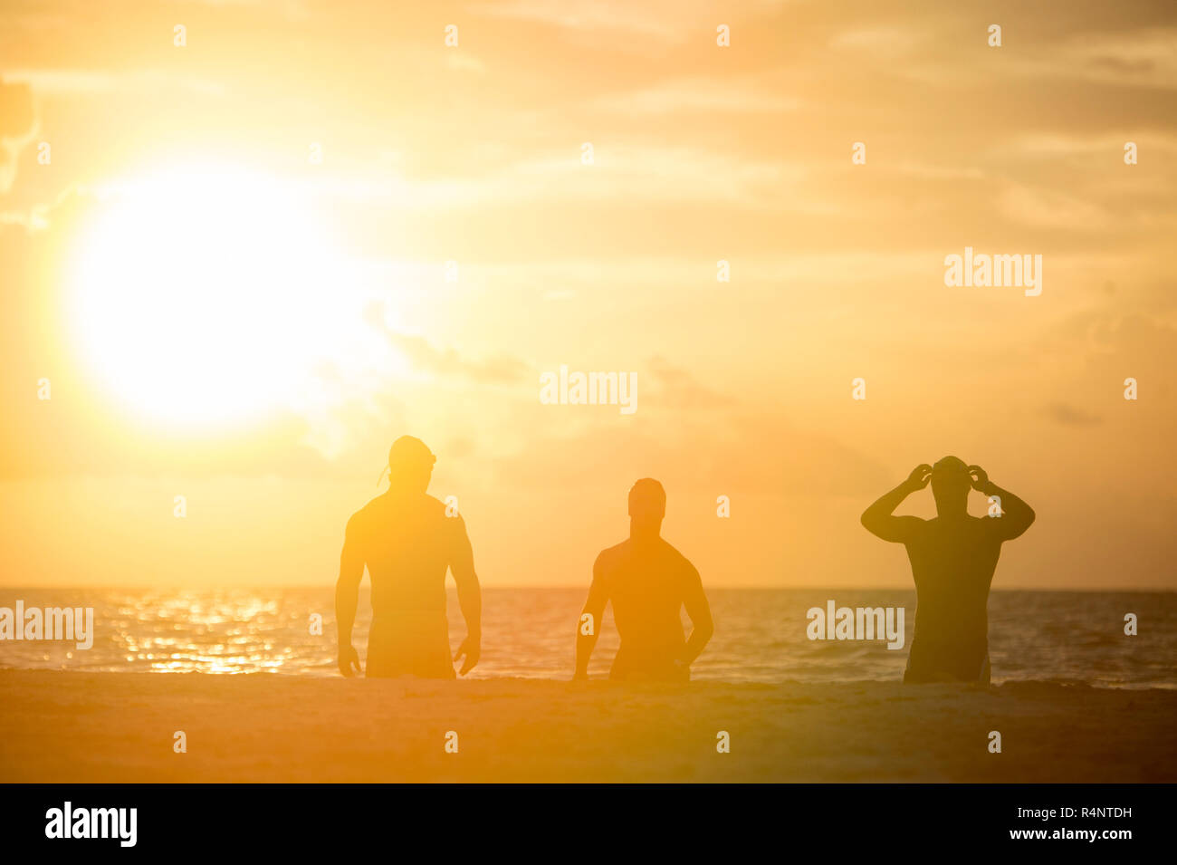 4cb853a5a03 View of silhouettes of three men in swimming caps on beach at sunrise, PlayaÂ