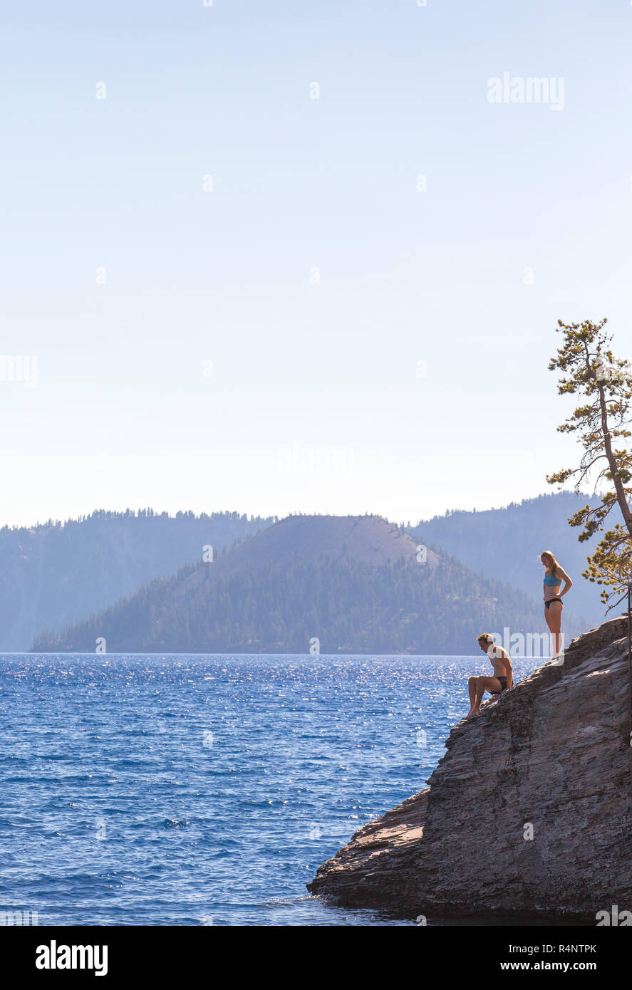 Distant view of man and woman in swimwear on shore of Crater Lake, Oregon, USA - Stock Image