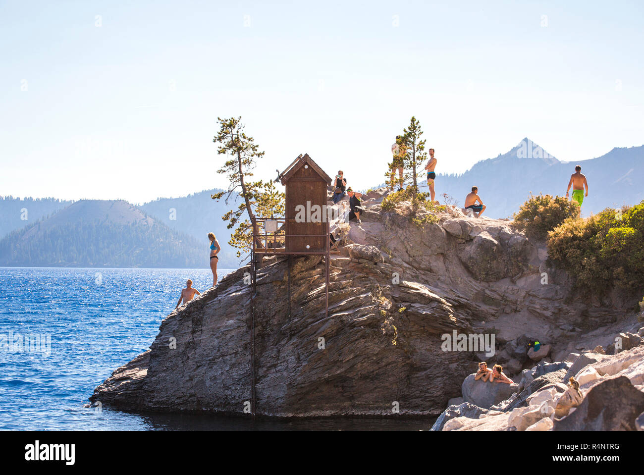 Swimmers wait on a rock outcrop surrounded by a big blue lake on sunny summer day, Crater Lake, Oregon, USA Stock Photo