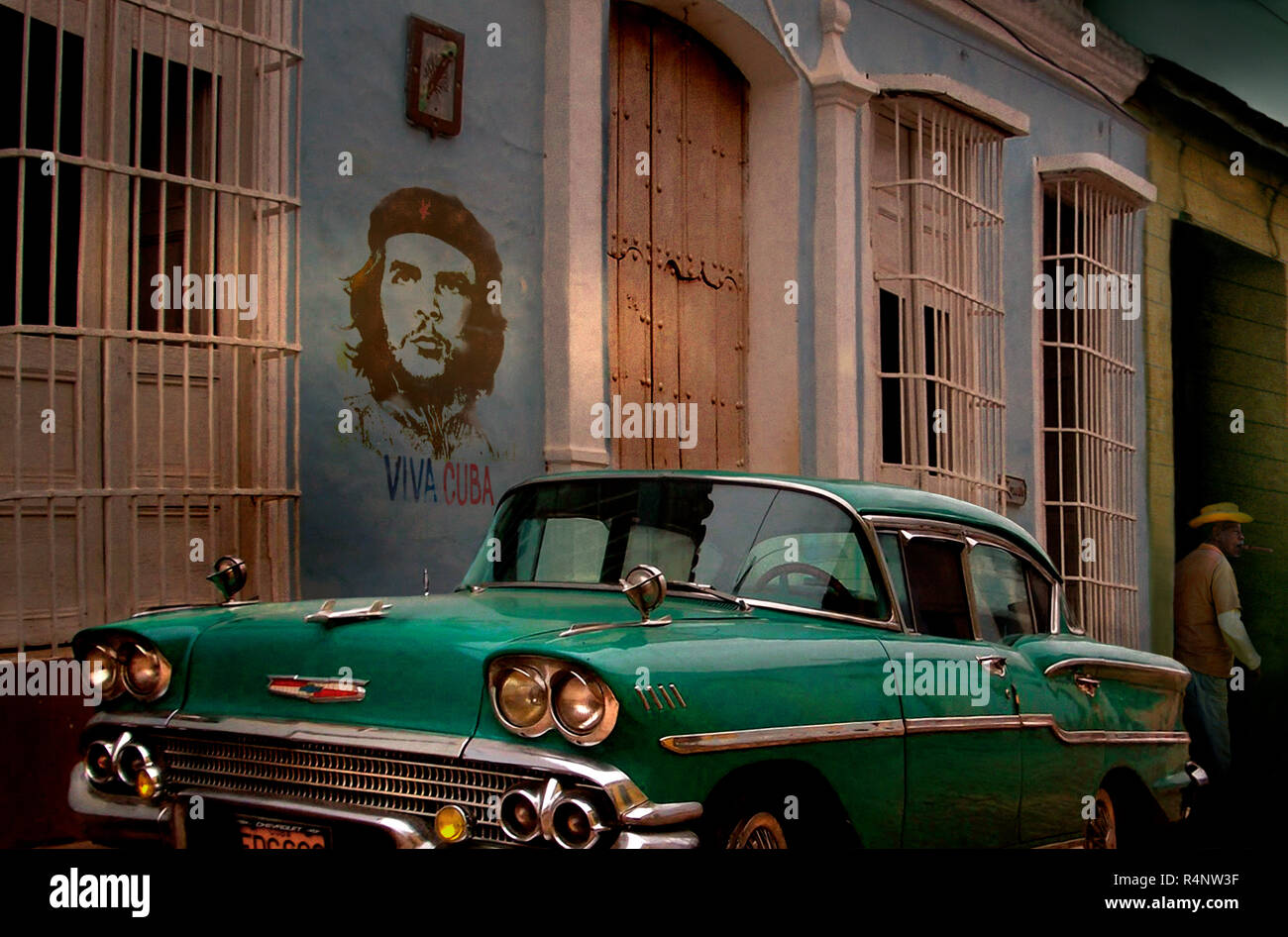 Vintage car and graffiti of Che Guevara in street, Trinidad, SanctiSpritusProvince, Cuba Stock Photo