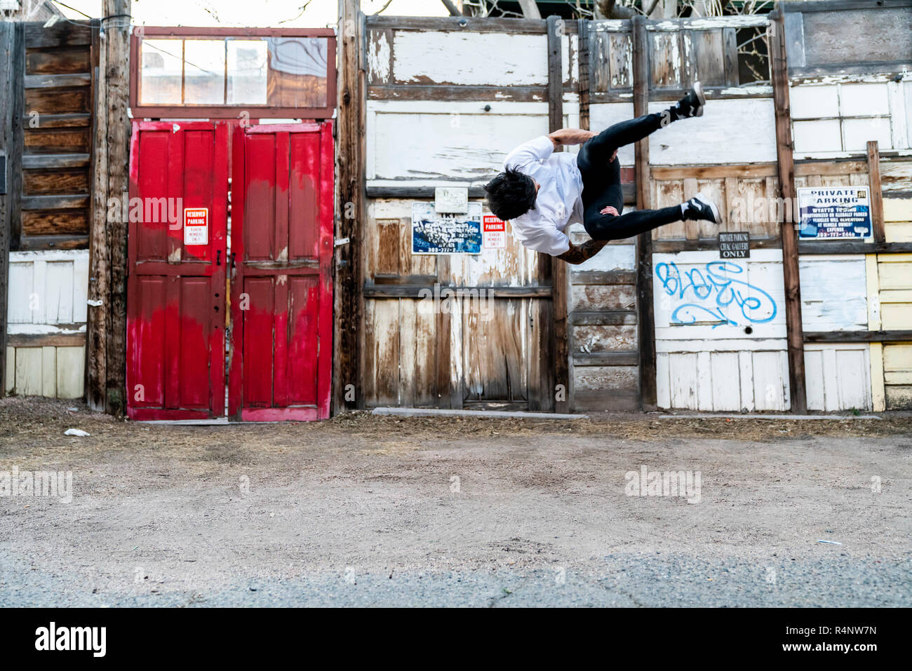A young fit parkour athlete in a side-flip in front of street art in Santa Fe Arts District of Denver, Colorado, USA - Stock Image
