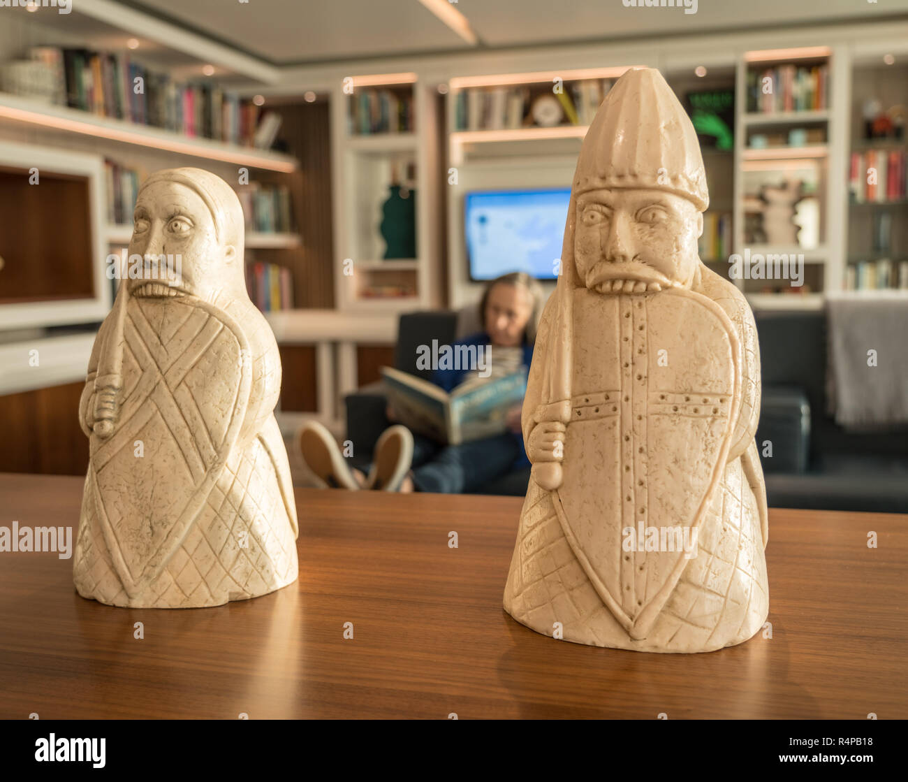 Traditional Lewis Chessmen on table in front of modern library - Stock Image