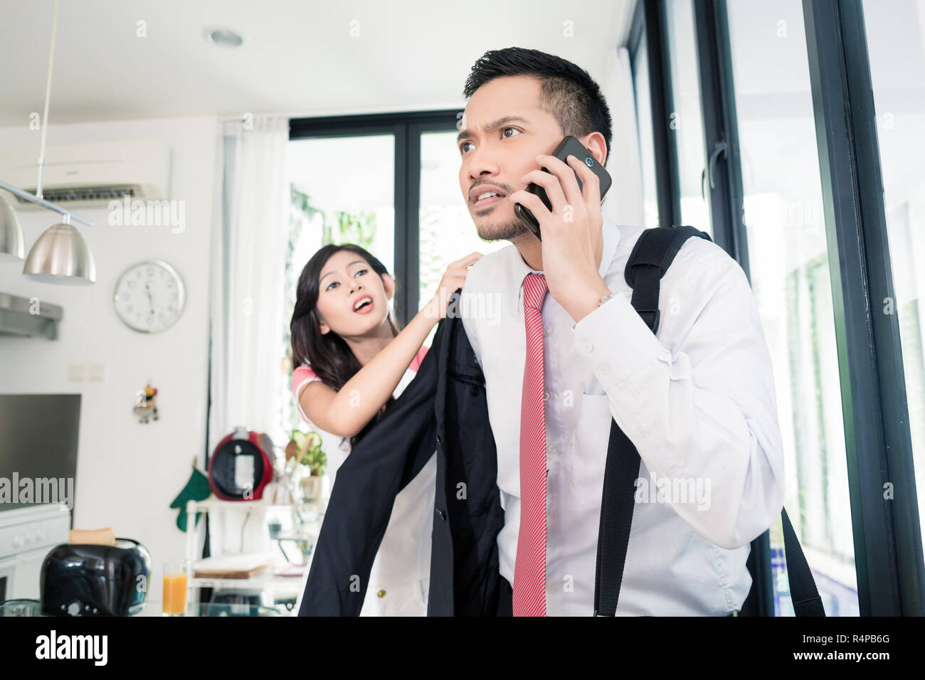 Wife helping man being late for work in jacket Stock Photo