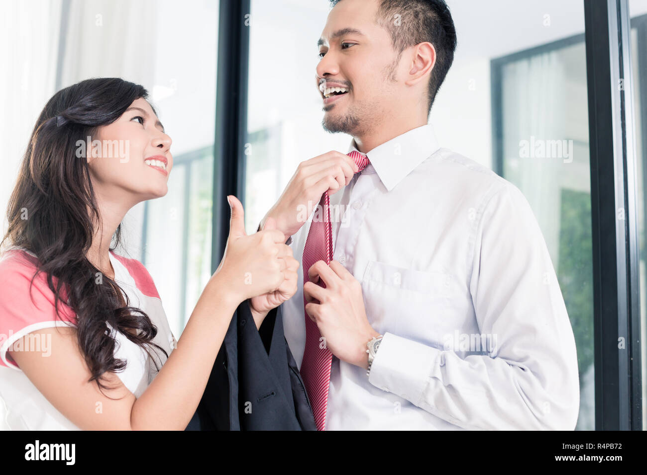 Wife helping her man going to office for work Stock Photo
