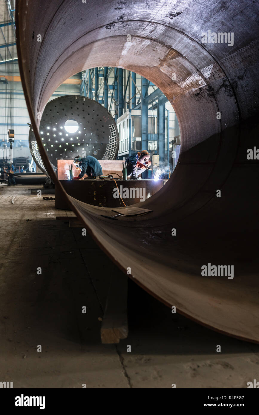 Two workers welding in a factory manufacturing boilers Stock Photo