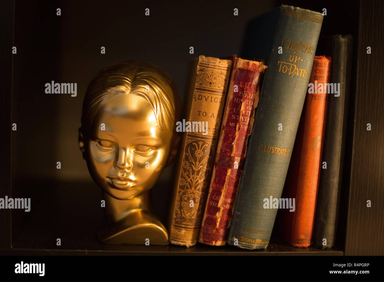 A gold bust of a girl next to old-fashioned books about etiquette and marriage. Stock Photo