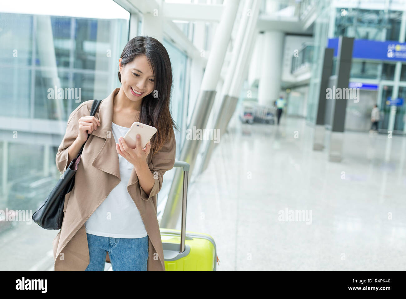 Woman check flight number on mobile phone in airport - Stock Image