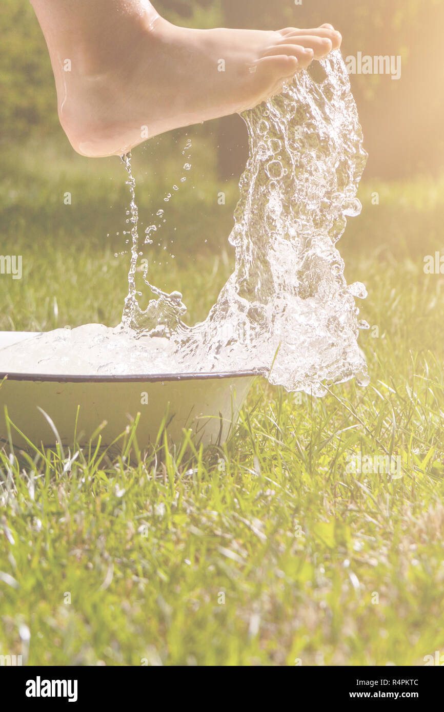 Little boy and splash of water in the summer garden - Stock Image