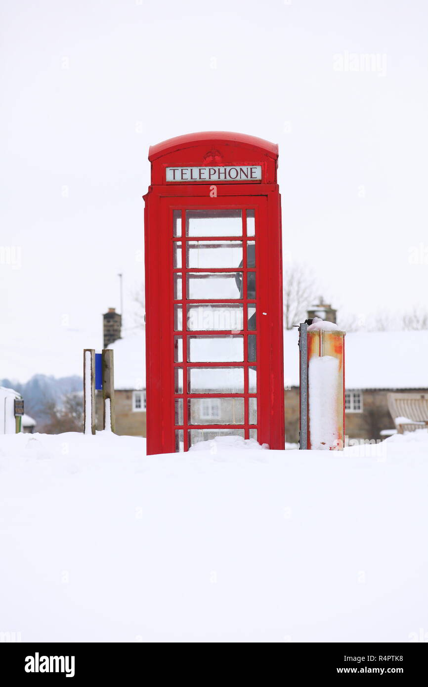 A K8 Red Telephone Box covered in snow at Goathland,North Yorkshire - Stock Image