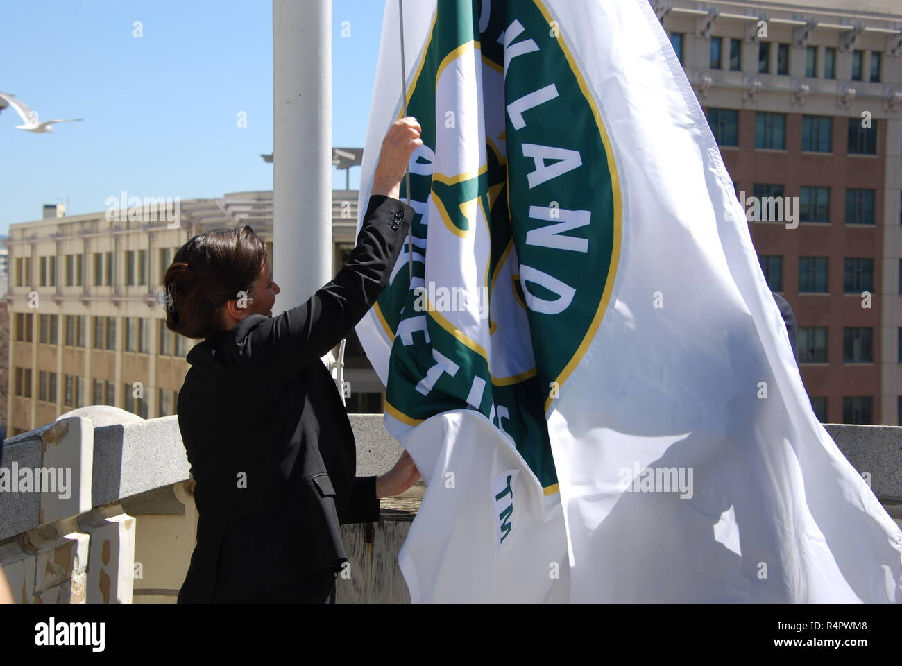 Oakland Mayor Libby Schaaf raises an Oakland A's flag on the roof of Oakland City Hall ahead of the 2018 Major League Baseball season. - Stock Image