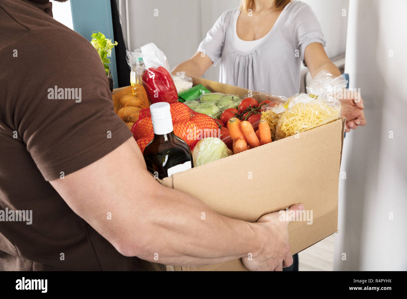 Delivery Man Giving Grocery Box To Woman - Stock Image