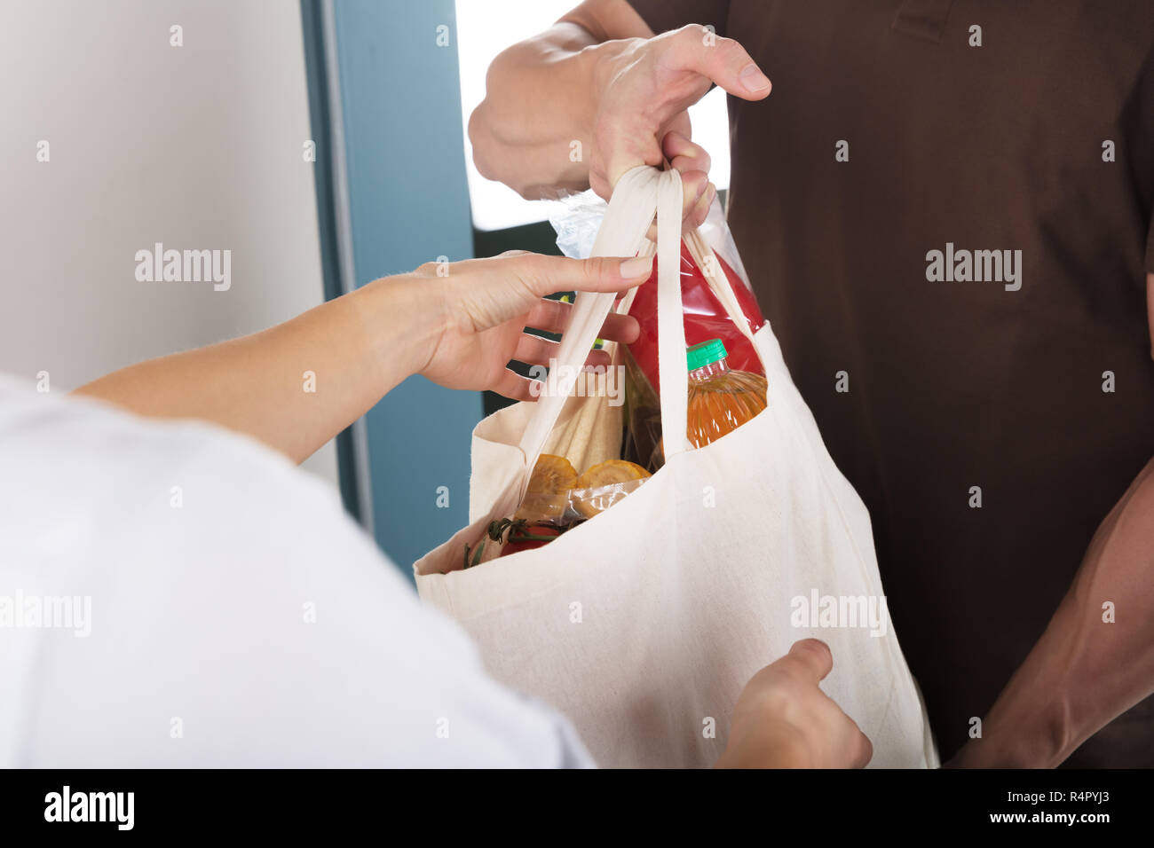 Man Giving Bag Of Grocery To Woman - Stock Image