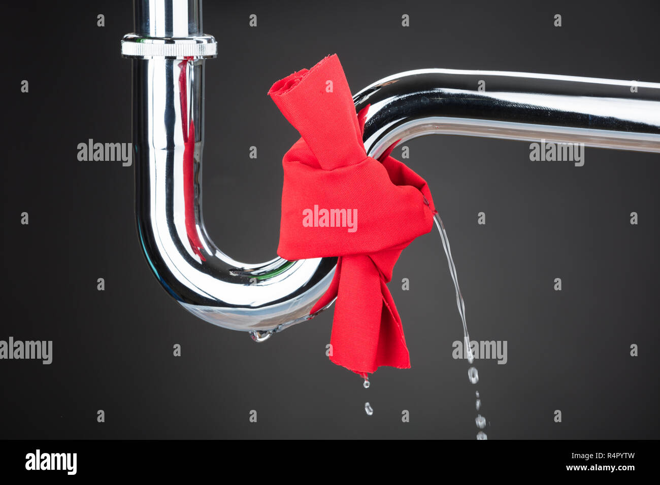 Red Cloth Tied On Leakage Pipe - Stock Image