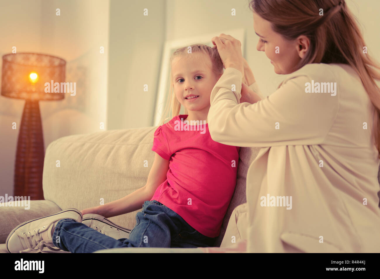Cheerful pleasant girl having her ponytails done - Stock Image