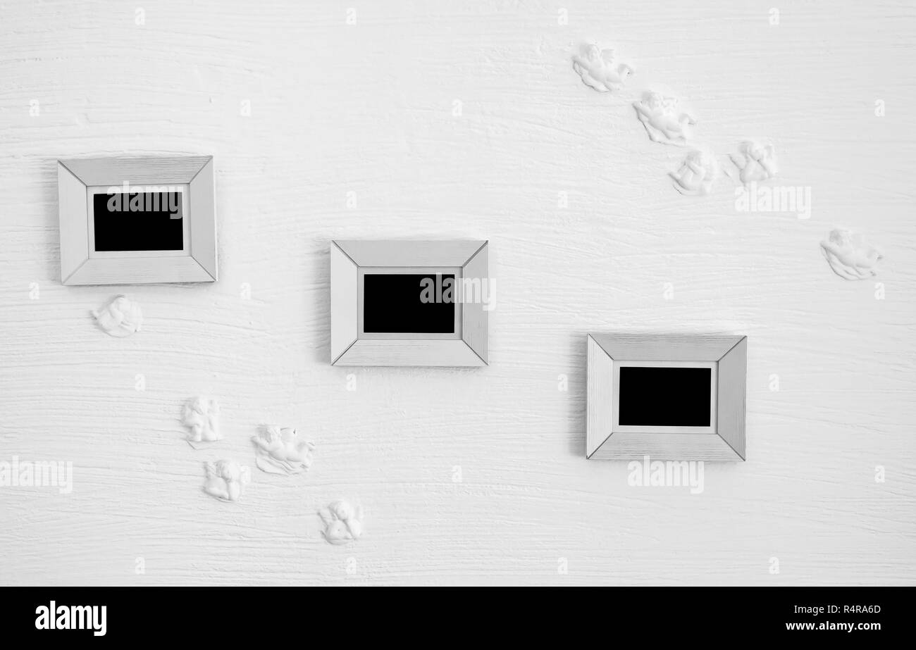 three white wooden photo frames on the wall - Stock Image