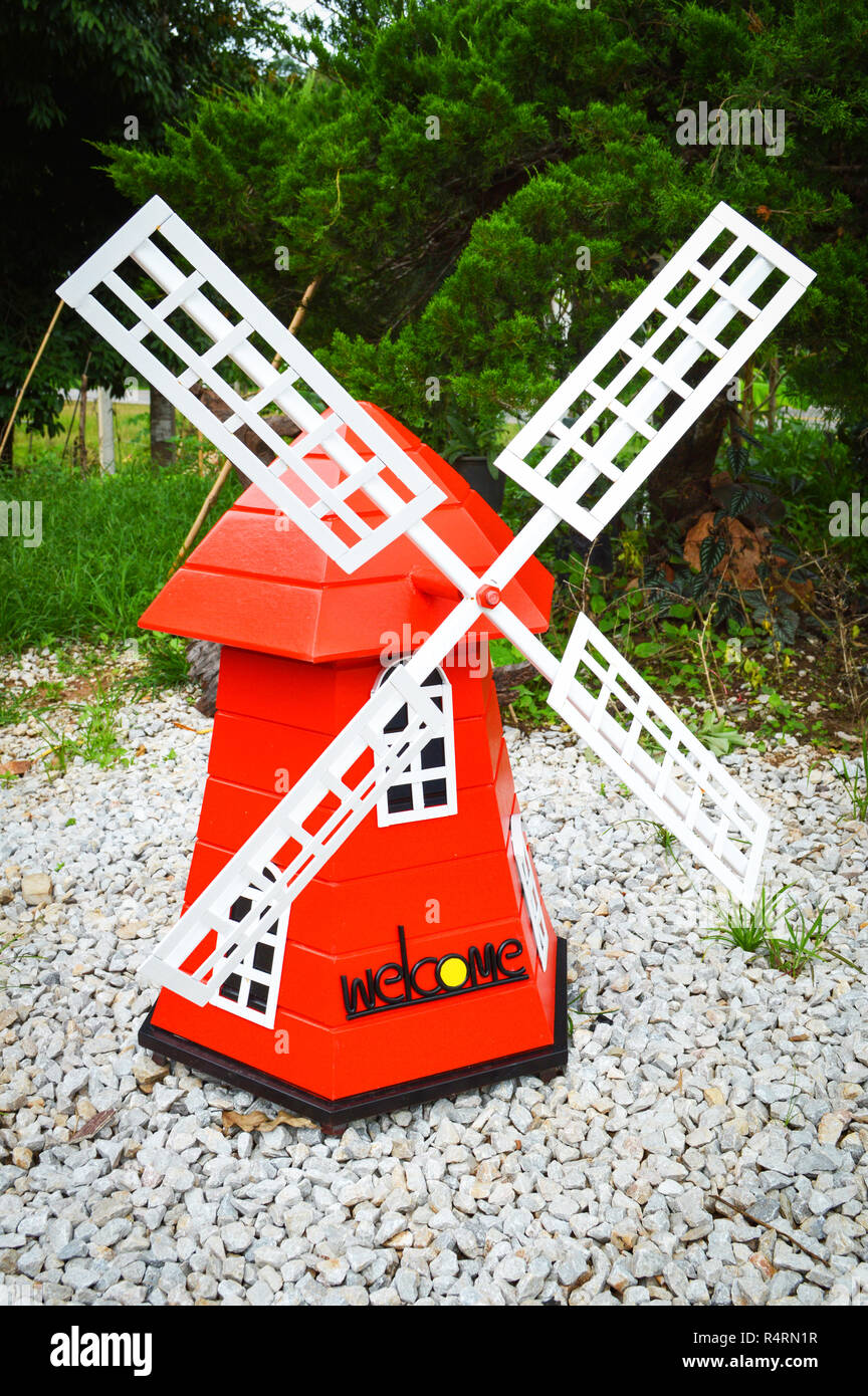 colorful red windmill wind turbine in the park garden - landscape windmill nature hill background Stock Photo