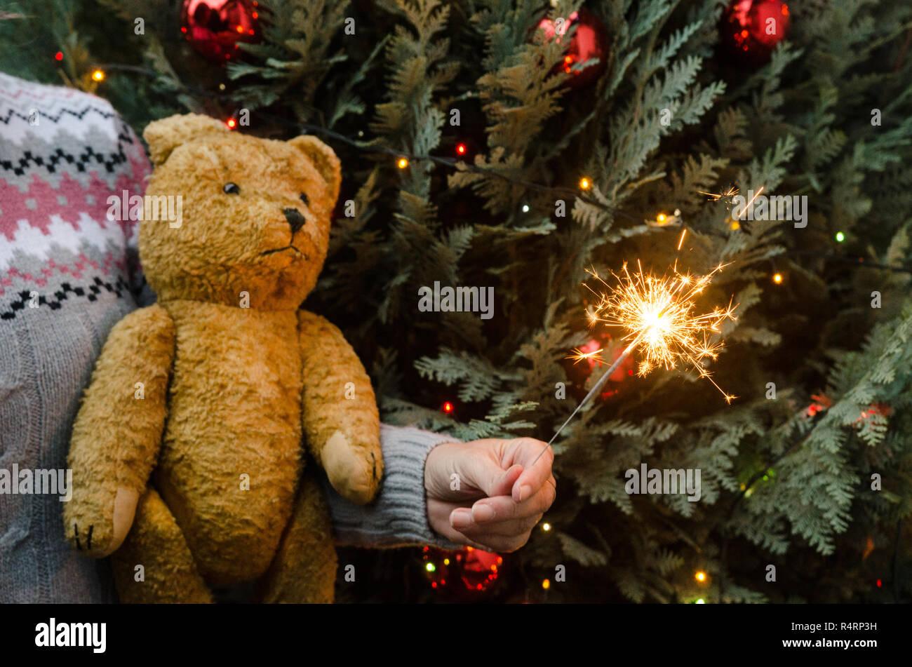d7e866f8fe Christmas scene - woman holding teddy bear and sparkler before christmas  tree