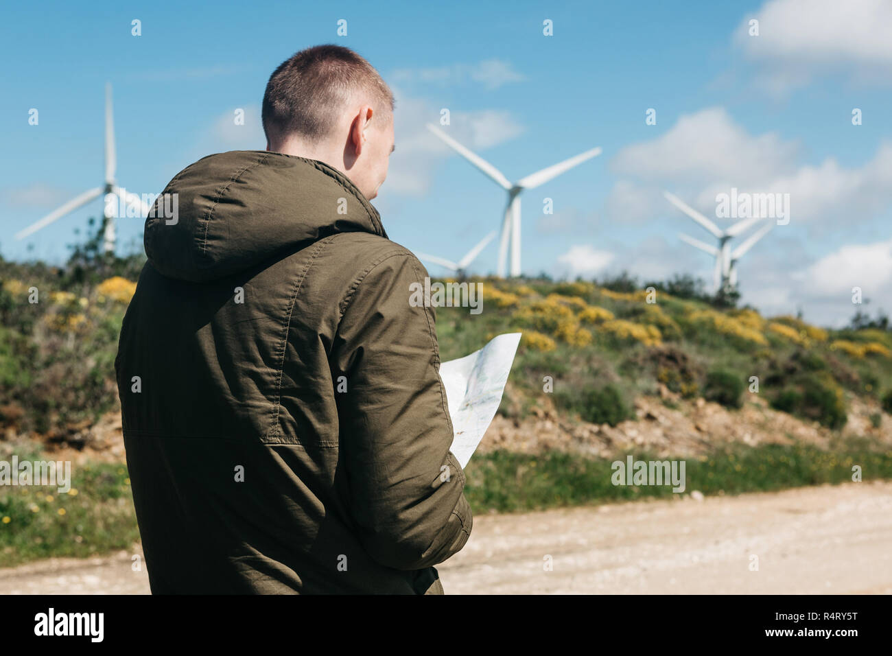 A tourist man looks at the map of the area for further travel. Unknown terrain or unfamiliar territory or path. - Stock Image