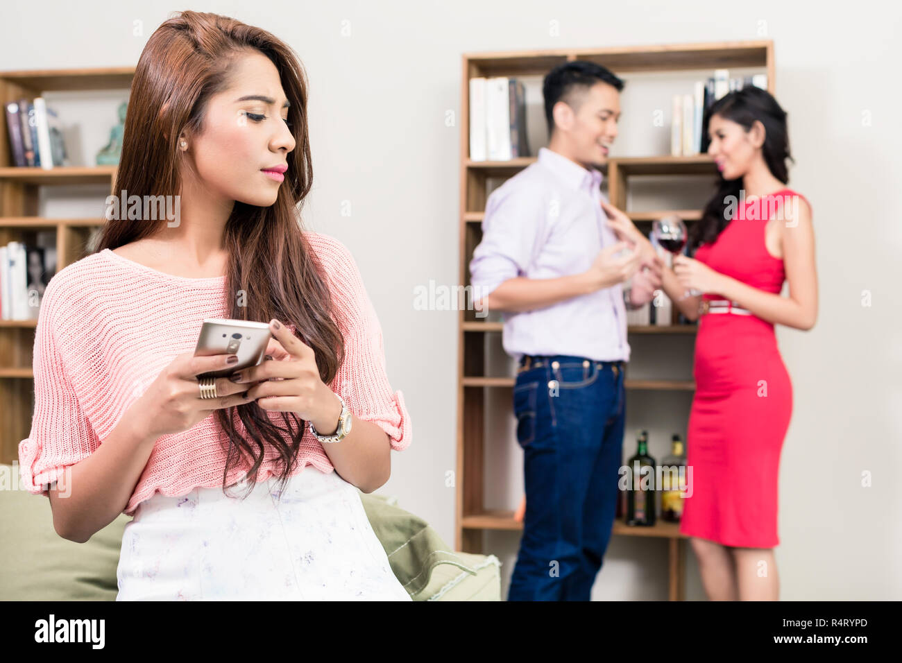 Woman looking at couple in the background - Stock Image