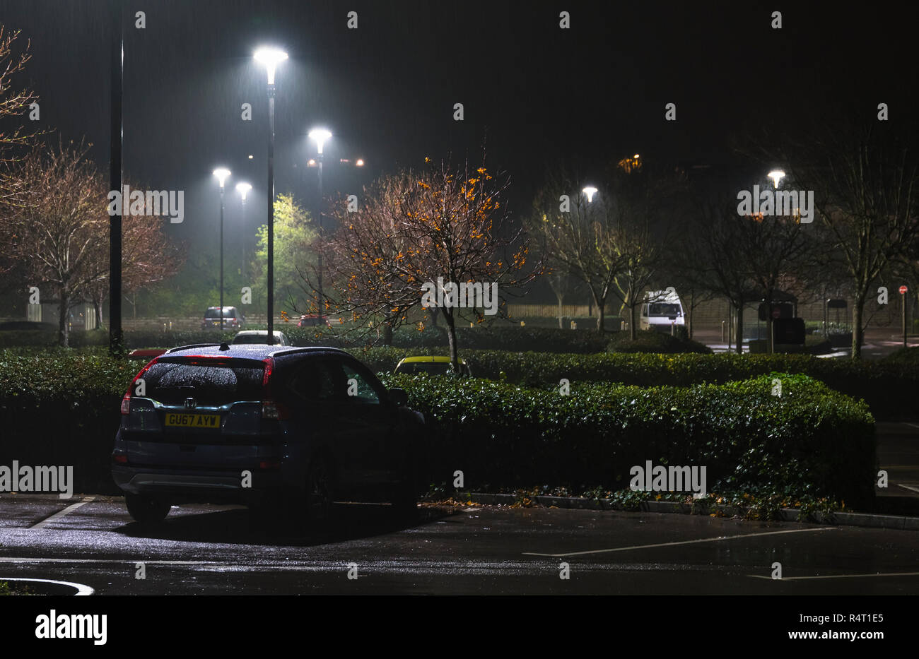Lit up car park at night while raining, with just a few parked cars still there, in the UK. Car park in rain. - Stock Image
