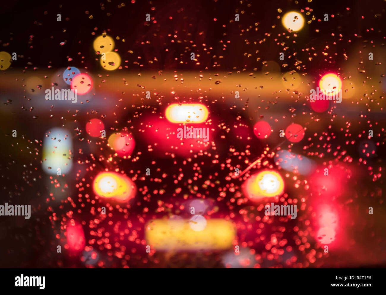Car in front braking hard in wet weather while rain falls on the road and windscreen. Vehicle braking hard while raining. Car stopping. - Stock Image