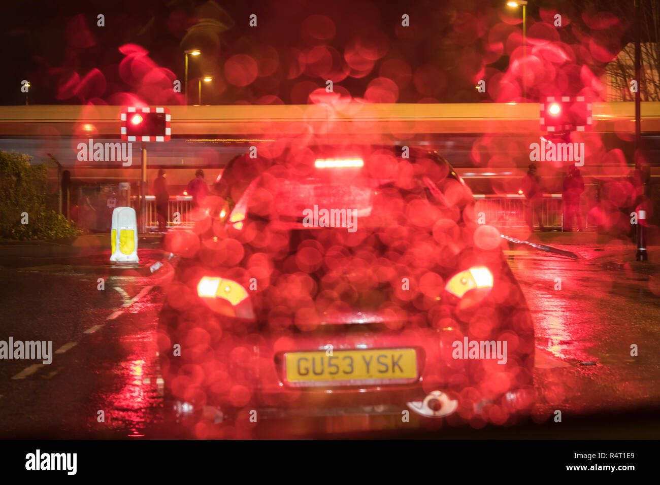 Cars waiting in line at a level crossing at night while raining, with a train moving over the crossing, in the UK. - Stock Image