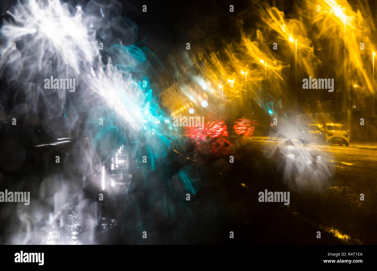 View through windscreen of cars driving in rain at night. Wet weather driving while raining. - Stock Image