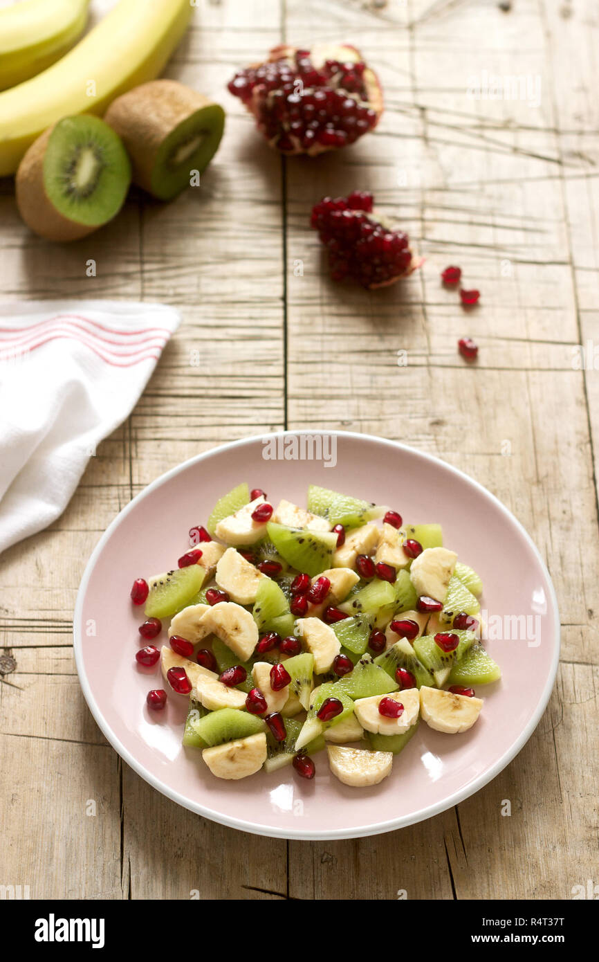Salad of slices of various fruits and pomegranate seeds on a wooden background. - Stock Image