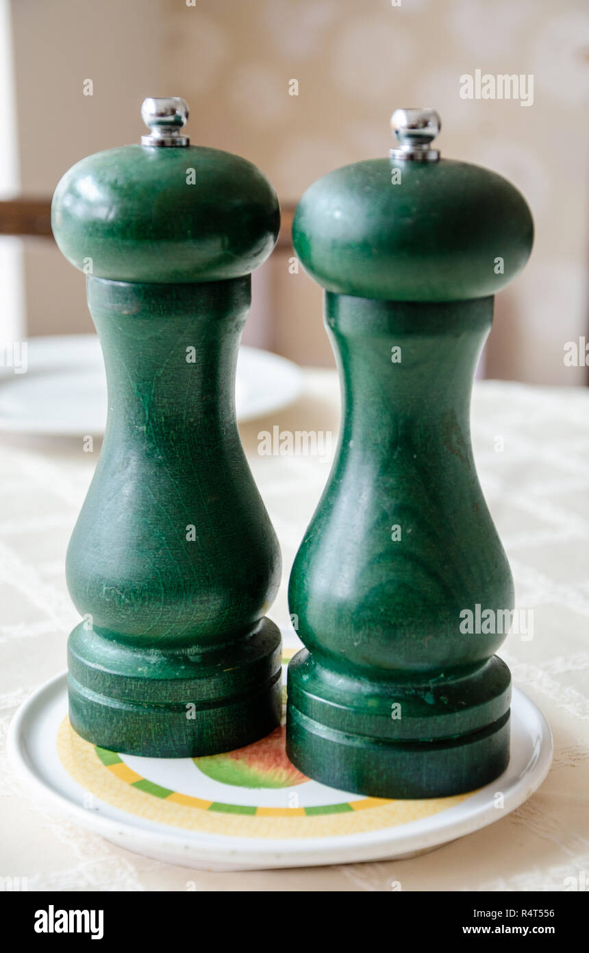 Salt and Pepper mills on a dining room table. - Stock Image